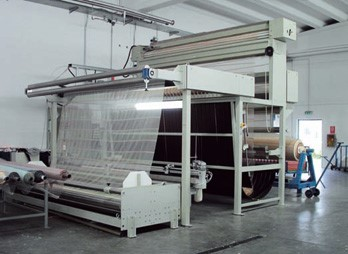 Complete preparation machine with: rolls conveyor, sewing stand, brushing system, fabric guide, exit for roll/plait.